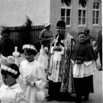 """Die Kornes """"Liesi"""" (Elisabeth) bei der Kommunion 1961 (Pfarrer Kalb mit Ministrant Thomas Müller). Im Hintergrund der damalige Kindergarten (Gelbes Haus)"""