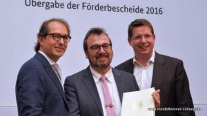 Bundesverkehrsminister Alexander Dobrindt (links) und Bundestagsabgeordneter Stephan Stracke (rechts) überreichen Bürgermeister Robert Sturm den Förderbescheid.