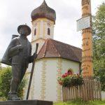 """In der Dorfmitte von Oberneufnach steht nicht nur die Kapelle St. Josef und der Maibaum, sondern auch ein Milchbauer aus Bronze. Die Figur soll daran erinnern, wie im 19. Jahrhundert die Milch zur """"Käskuch"""" gebracht wurde, die hier früher stand. Bild: Augsburger Allgemeine"""