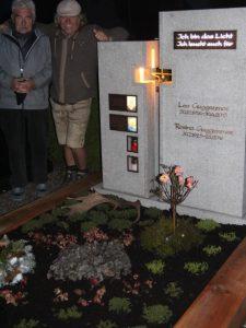 Steinmetz Gerhard Schröder und Manfred Guggenmos präsentieren stolz das Grab, das sie gemeinsam geschaffen haben. Es ist per Solarstrom beleuchtet und sorgt selbst für die Bewässerung. Foto Mindelheimer Zeitung